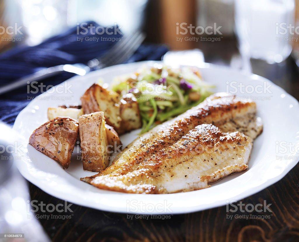 Tilápia frita com salada de repolho asiática e batatas assadas - foto de acervo