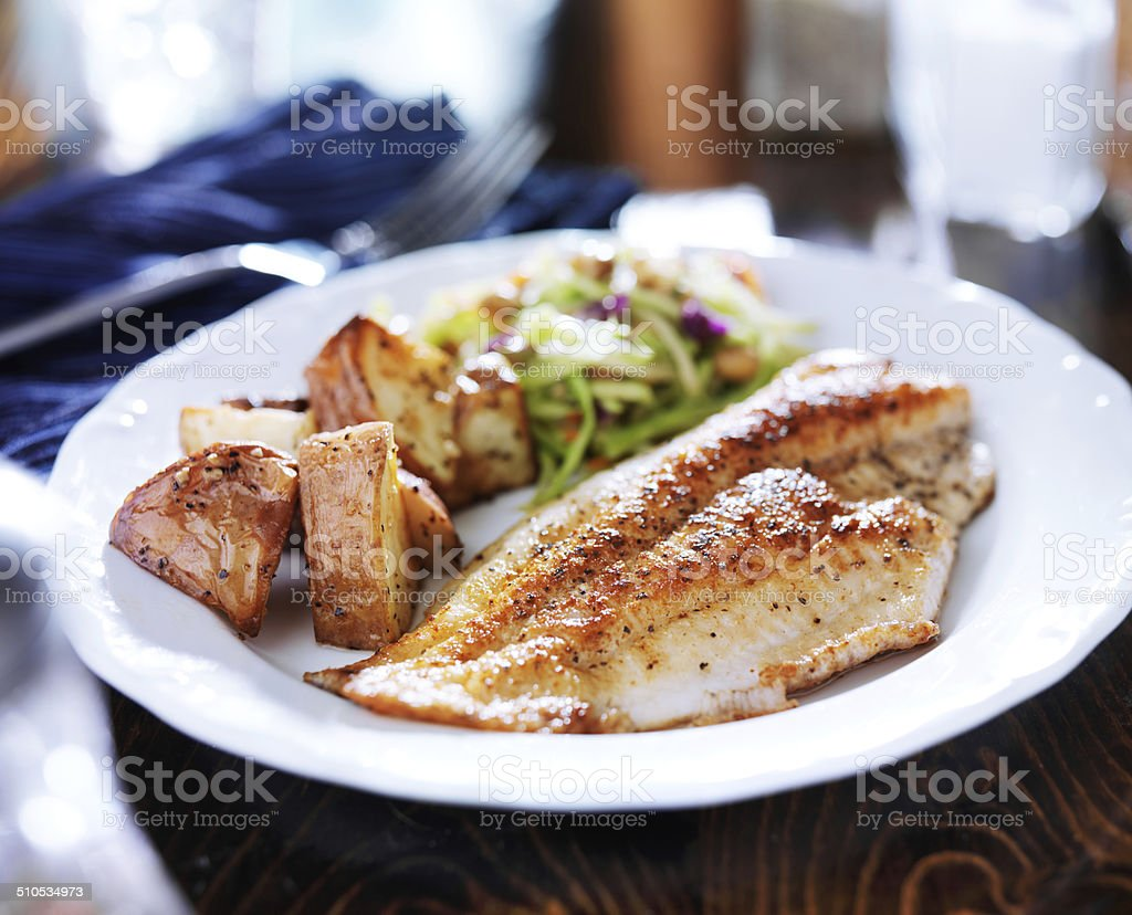 tilapia con pan asian slaw fritos y patatas asadas - foto de stock