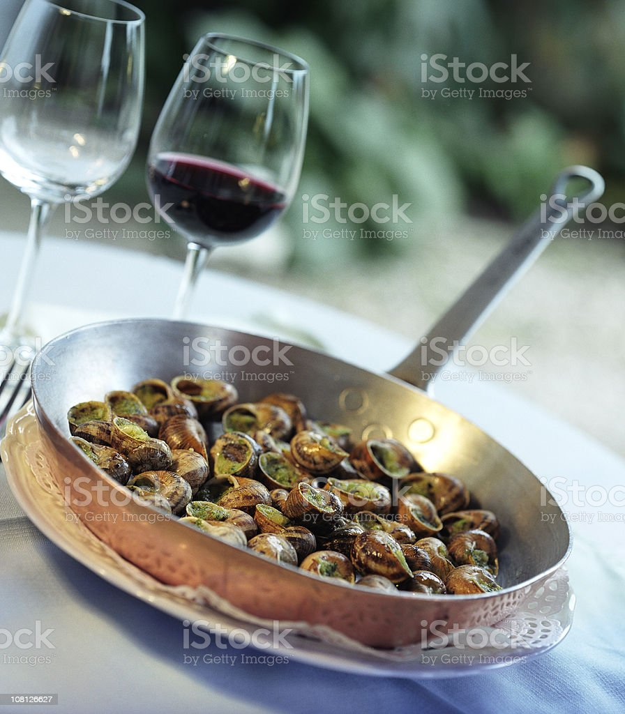 Pan of Escargot Snails on Table with Wine Glasses royalty-free stock photo
