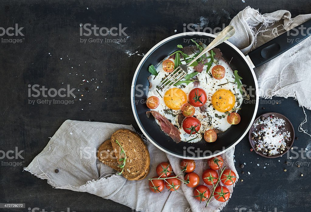 Pan of fried eggs, bacon and cherry-tomatoes with bread stock photo