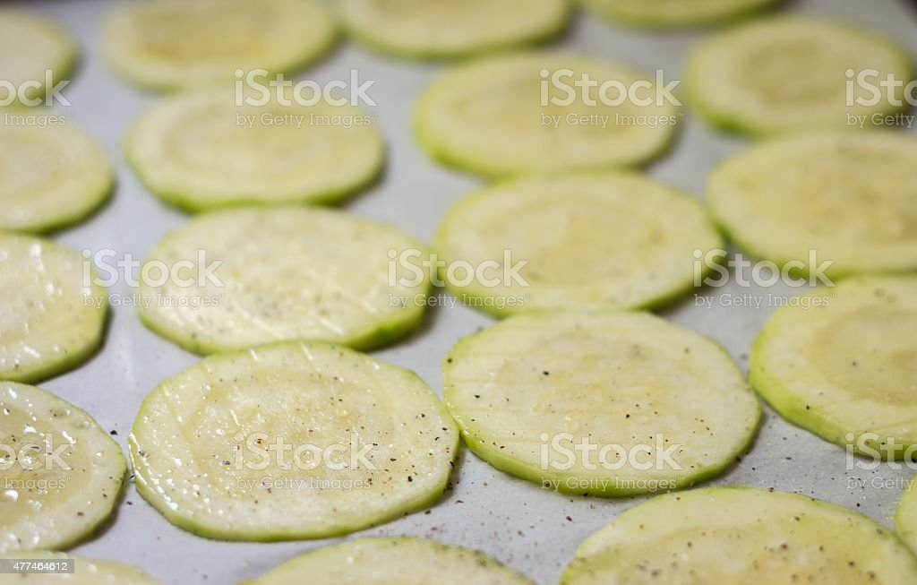 pan of raw zucchini chips waiting to be baked. stock photo
