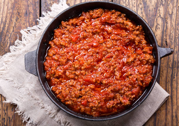 pan of sauce bolognese on wooden table stock photo