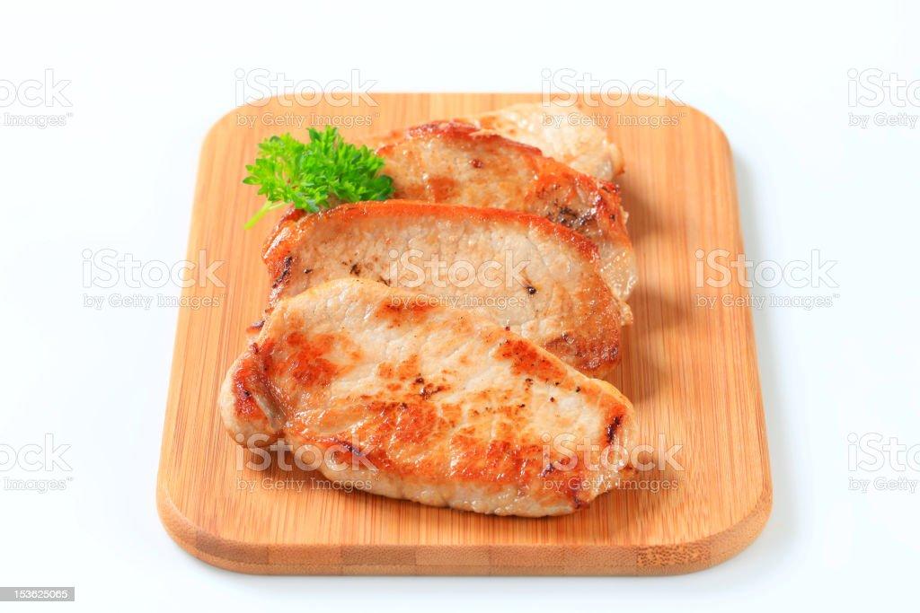 Pan seared pork cutlets on cutting board stock photo