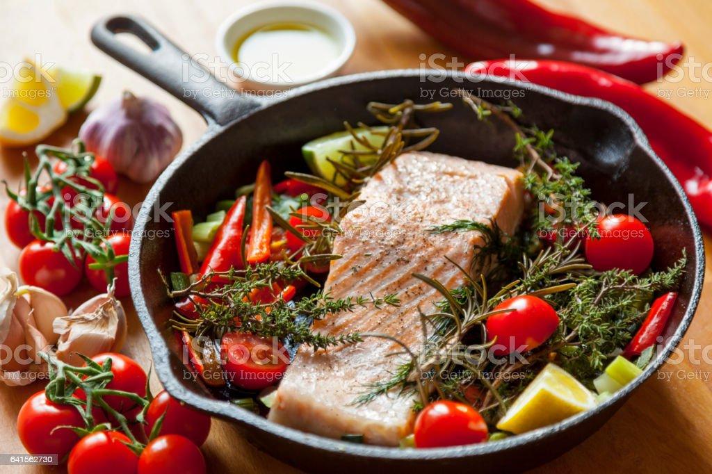 Pan Seared Salmon Steak in Steel Skillet with Fresh Vegetables stock photo