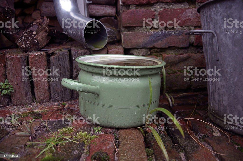 Pan under a rainpipe stock photo