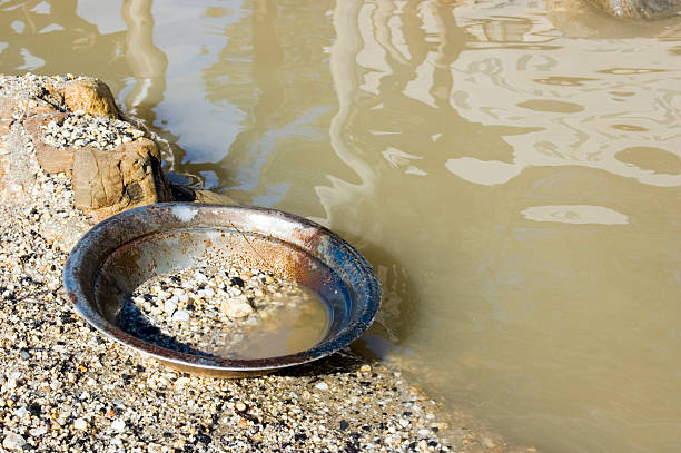 A pan used for finding gold sitting by water stock photo