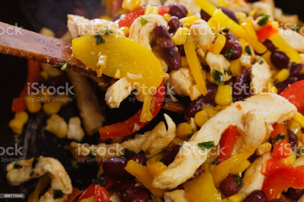 Pan with roasted vegetables and chicken for burritos close-up of cooking burrito. stock photo