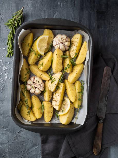 pfanne mit reihenkartoffel mit knoblauch, thymian und rosmarin auf strukturiertem grauem hintergrund - knoblauchkartoffeln stock-fotos und bilder