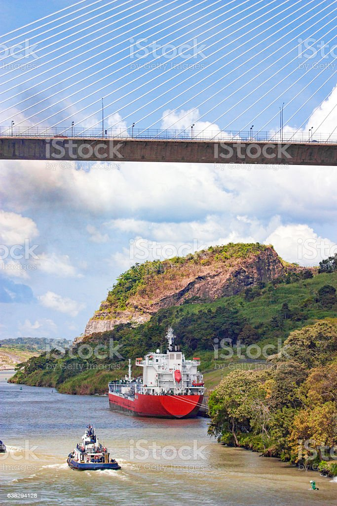 Panama Canal With Cargo Ship and Tugboat Under Centennial Bridge stock photo