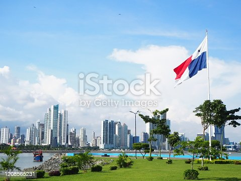 Panama City / Panama - September 1 2019: City skyline with green grass and flag flying. Blue sky and white clouds.