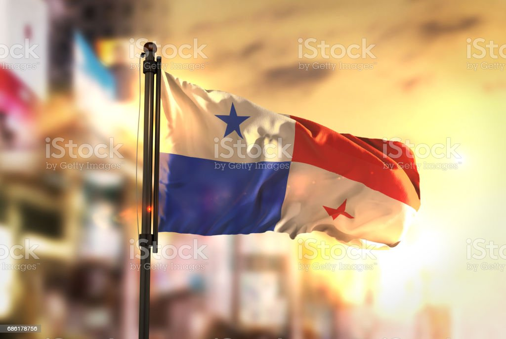 Panama Flag Against City Blurred Background At Sunrise Backlight stock photo