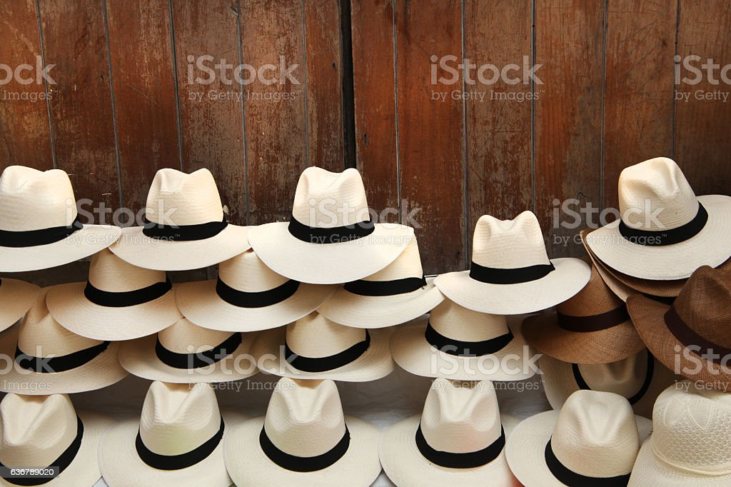 Panama hats piled up against a wooden door, Cartagena, Colombia. stock photo