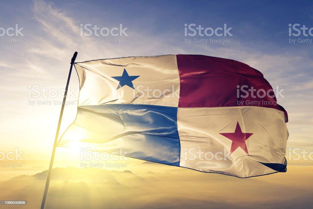 Tela de pano têxtil bandeira do Panamá Panamá acenando do nevoeiro de névoa superior ao nascer do sol - foto de acervo