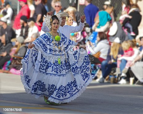 Young Panamanian woman dances during the Tournament of Roses in Pasadena. The woman is wearing a traditional Panamanian folklore dress or 'Pollera' and jewelry.