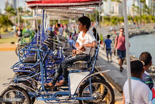 Panama City / Panama - March 25, 2016: Panamanian woman with short curly hair sitting on pedal cars next to promenade with people strolling