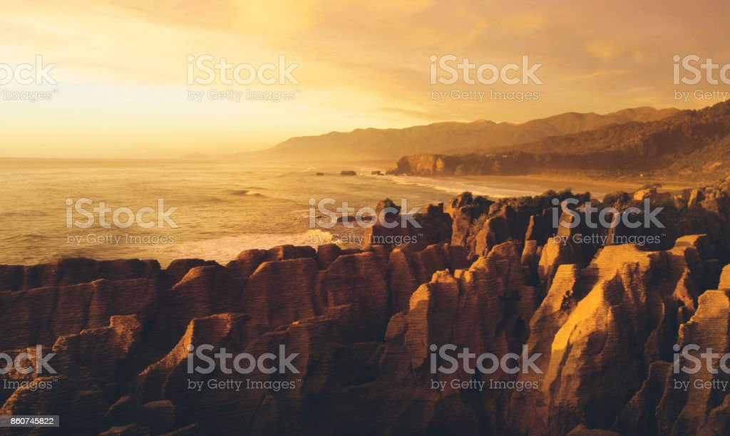 Panaroma of pancake rocks in the scenic view of mountains, beach and sunset. stock photo