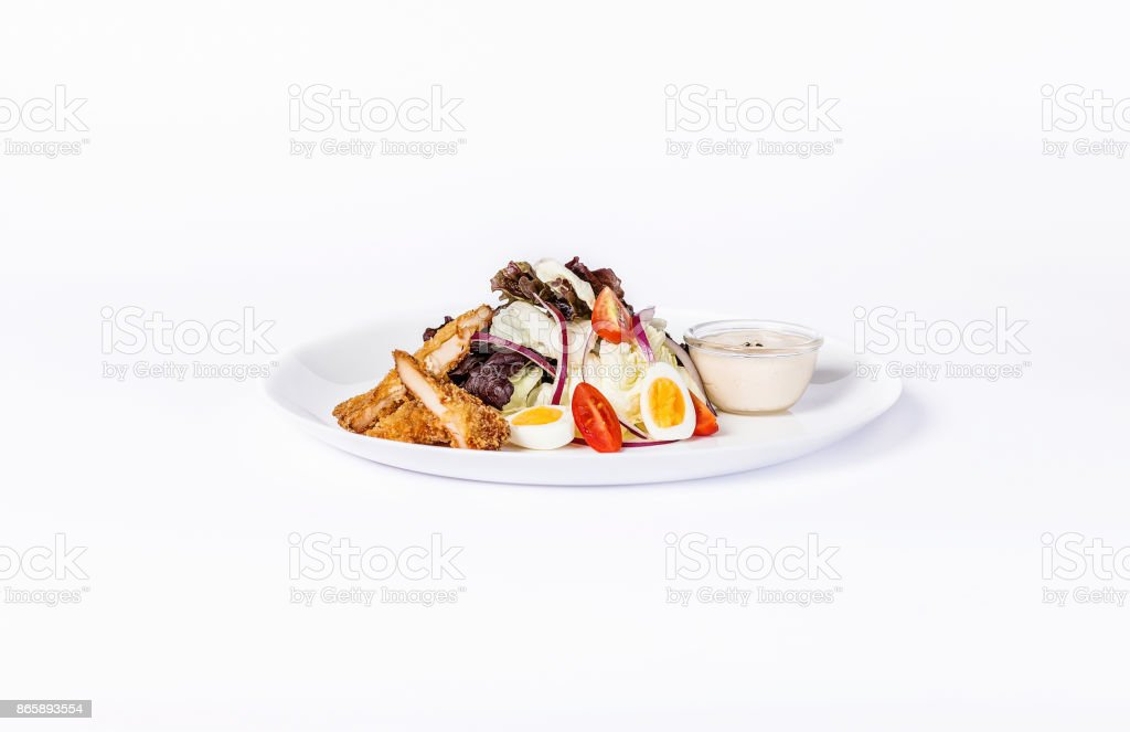 Pan-Asian salad, vegetables and eggs with fried chicken. On a white plate on a white background stock photo
