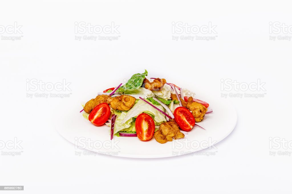 Pan-Asian salad, vegetables with fried chicken in batter. On a white plate on a white background stock photo