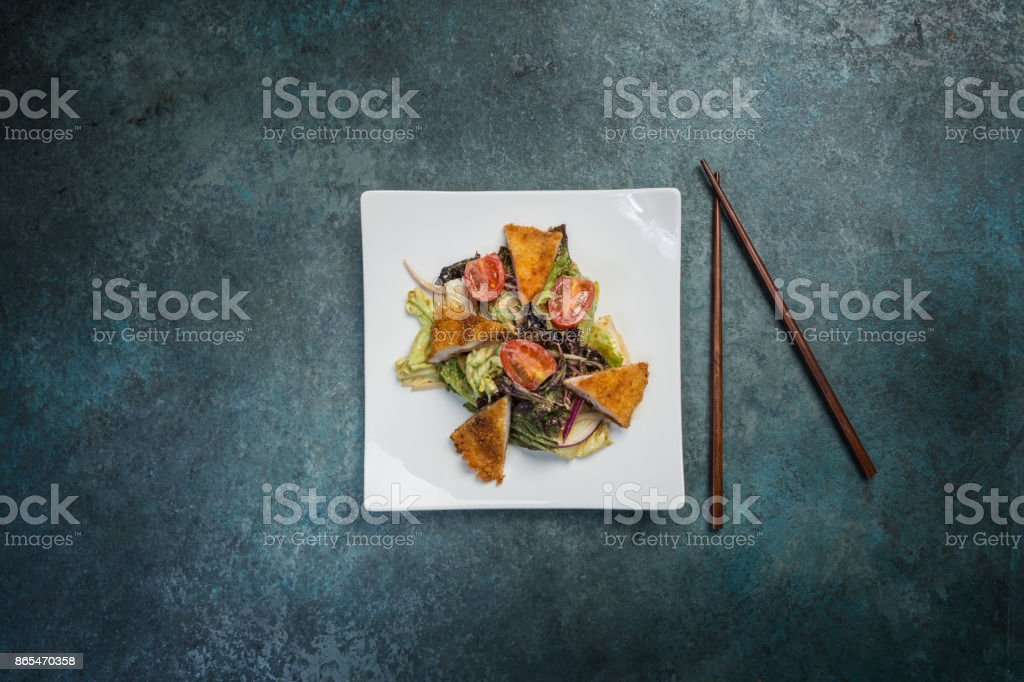 Pan-Asian salad, vegetables with fried chicken. On a square white plate with chopsticks. Top view stock photo