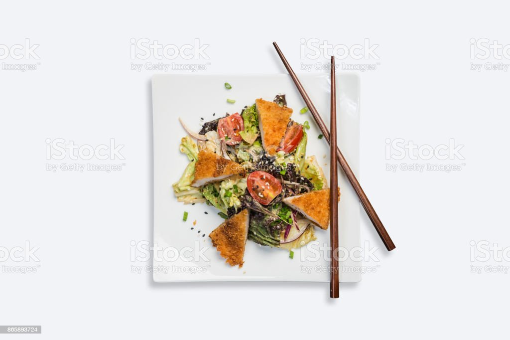 Pan-Asian salad, vegetables with fried chicken. On a square white plate with chopsticks on a white background. Top view stock photo
