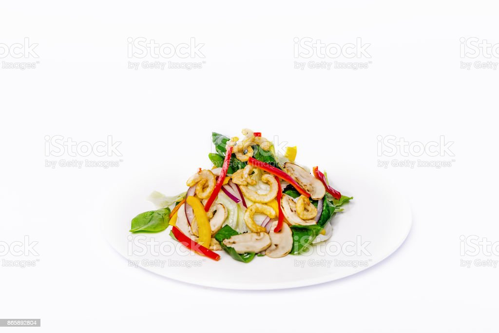 Pan-Asian salad, vegetables with fried squid rings. On a white plate on a white background stock photo