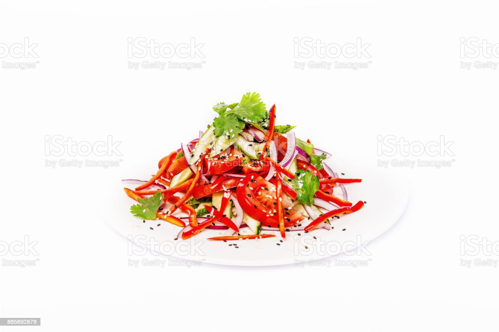 Pan-Asian spicy salad with red pepper and vegetables and sesame seeds. On a white plate on a white background stock photo