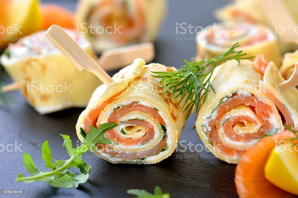 Pancake and salmon rolls stock photo