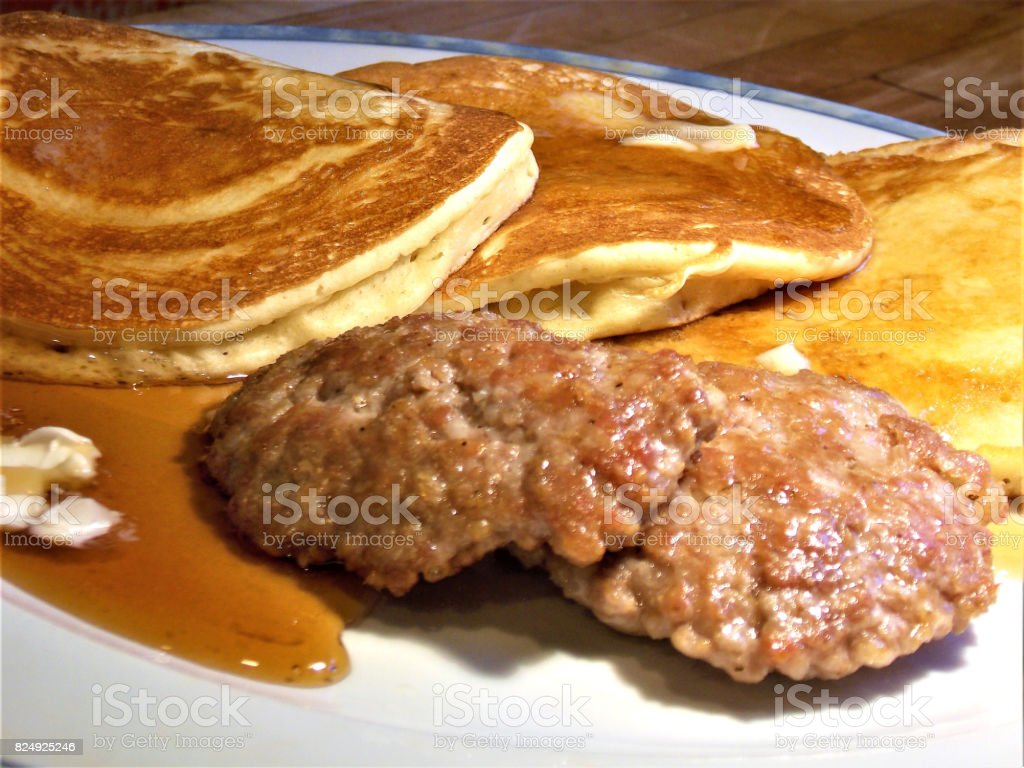 Pancake Breakfast Smothered in Butter & Rich Maple Syrup with Two Sausage Patties stock photo