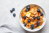 istock Pancake cereal with butter and berries in a white bowl, tiny pancakes, top view, copy space. 1226987291
