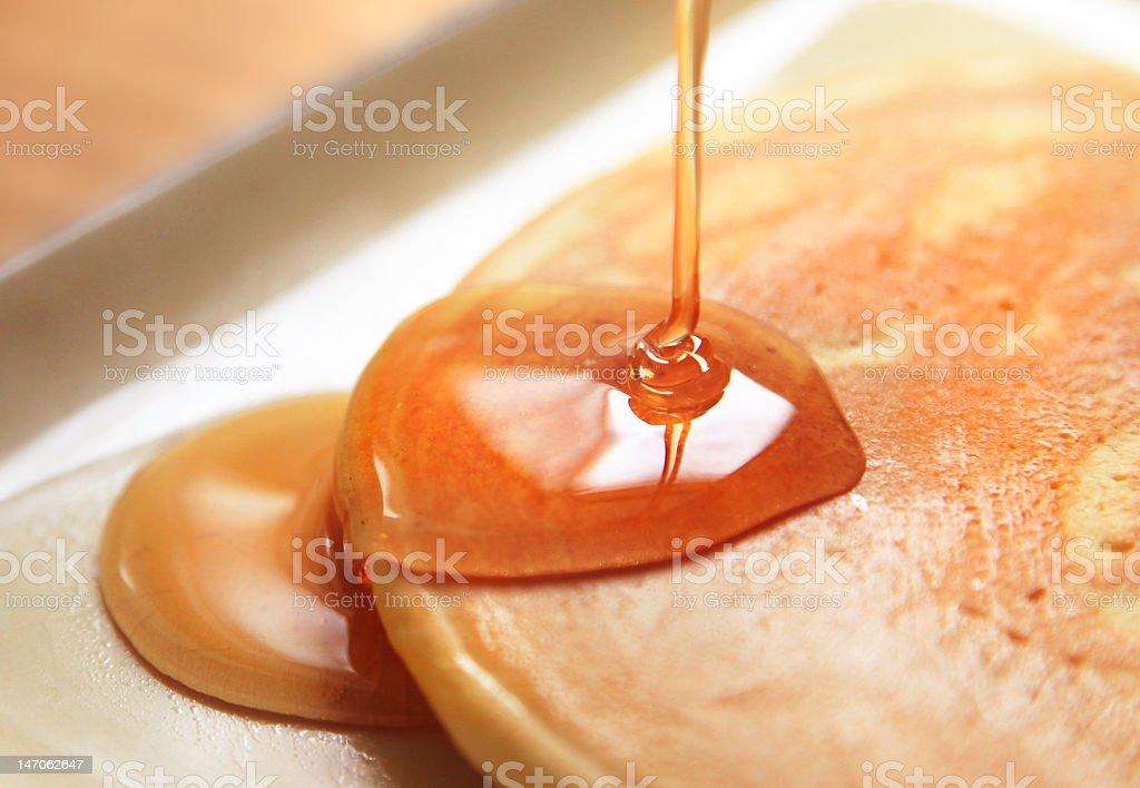 A pancake having syrup drizzled on to it stock photo