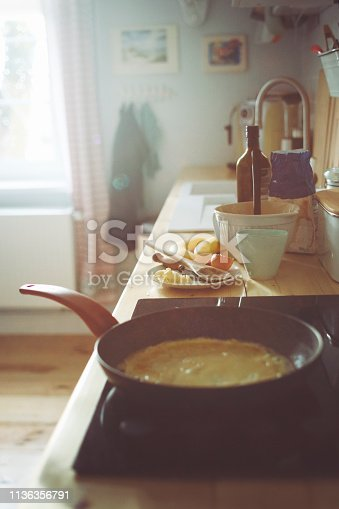 Pancake preparation in a large pan with banana in the light kitchen