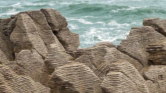 Pancake rocks along the coast of South Island, New Zealand, near Punakaiki. Close-up of the rocks; sea in the distance.