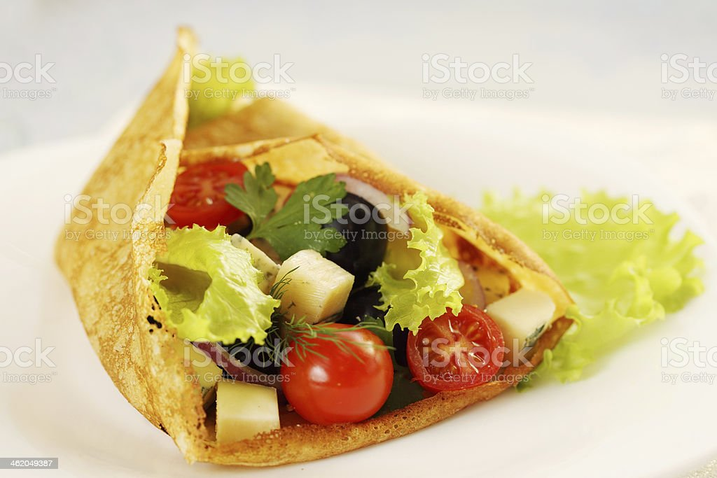 Pancake stuffed with salad stock photo