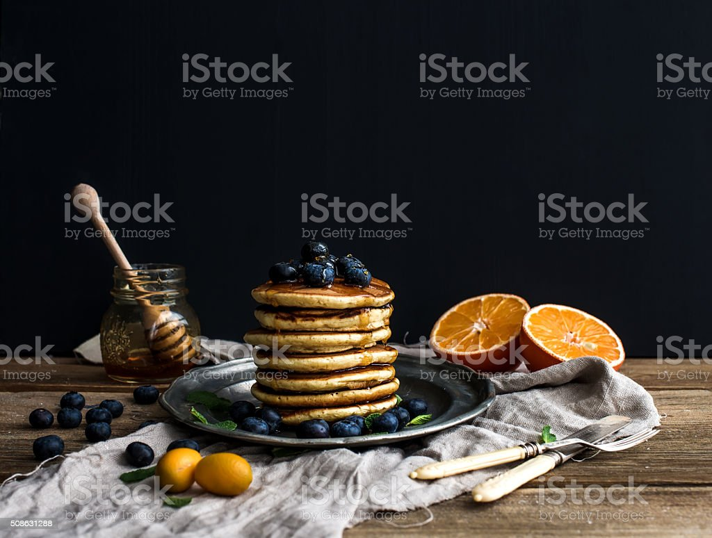 Pancake tower with fresh blueberries, oranges and mint on a stock photo