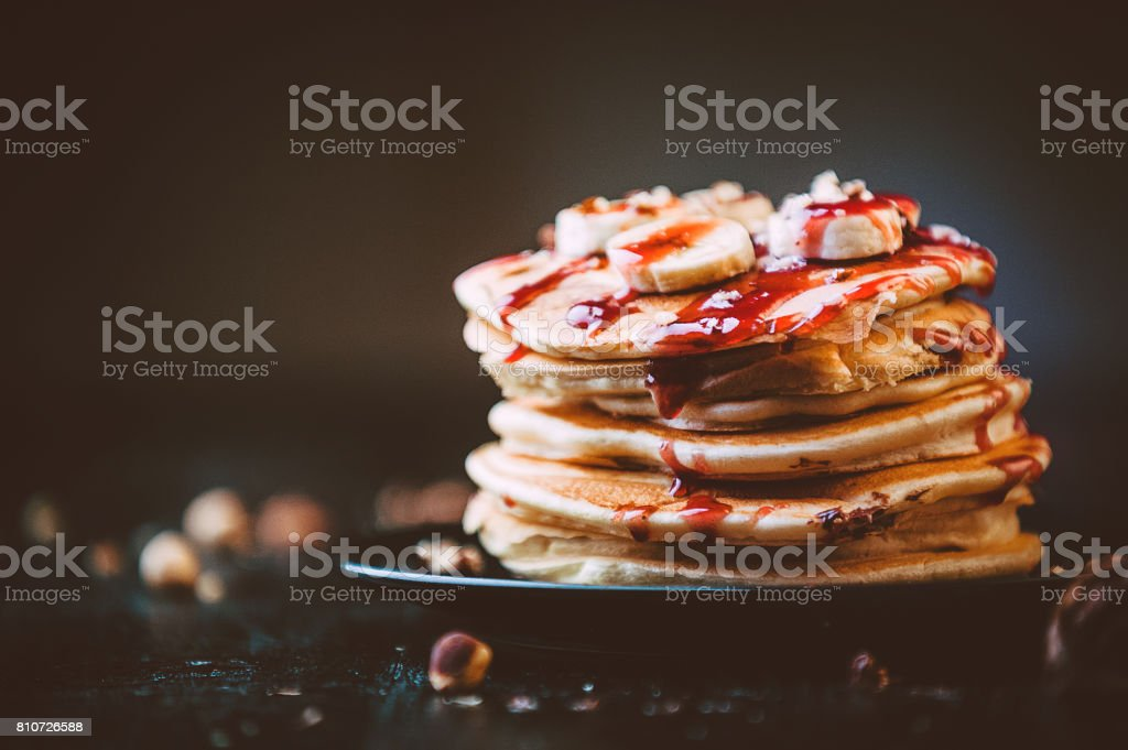 Pancake with chocolate and nut paste, walnuts and banana on a black plate stock photo