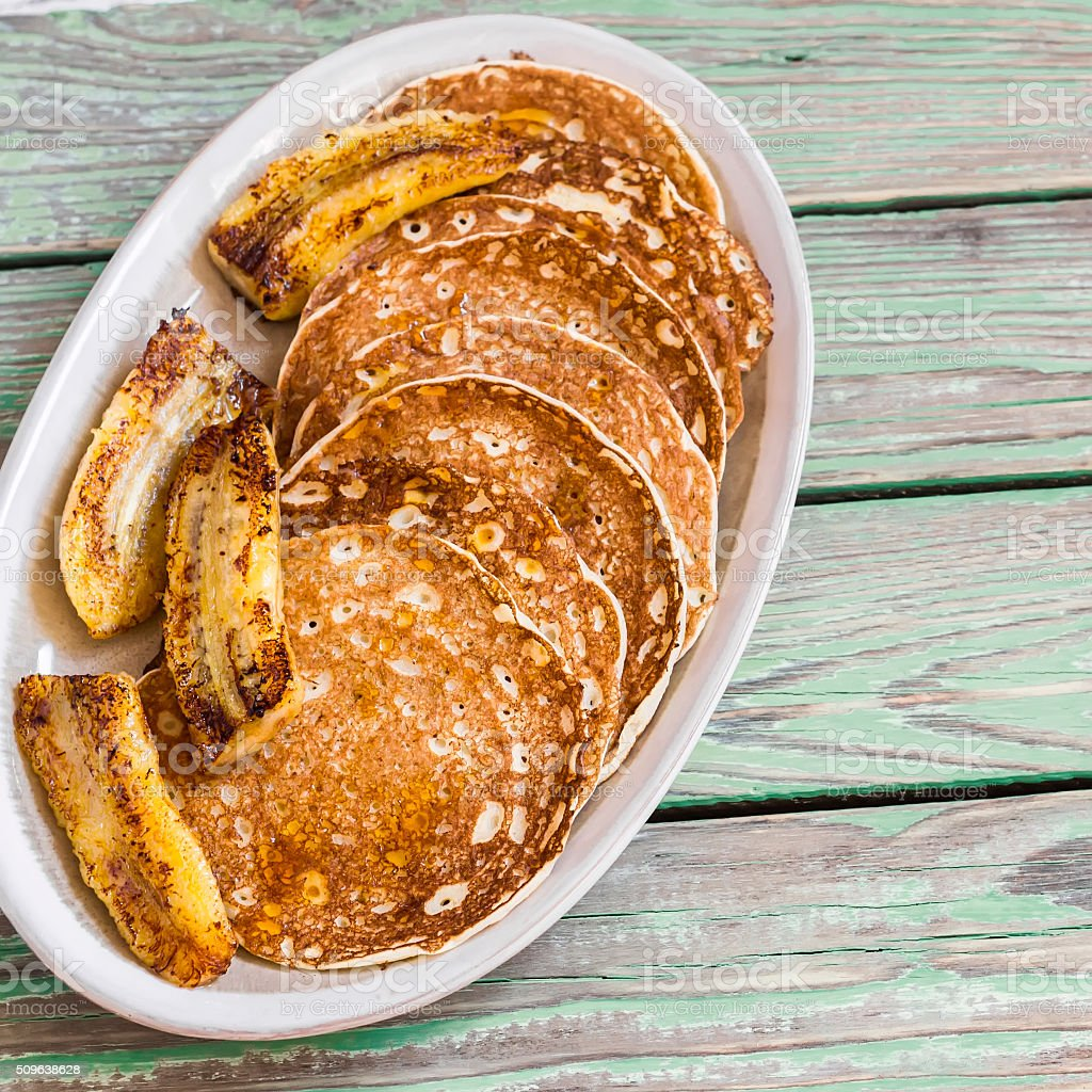 Pancake with fried banana, maple syrup and almonds. Delicious food stock photo