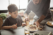 Father with two kids preparing pancakes at home