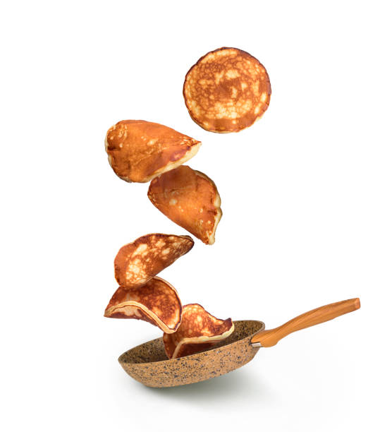 pancakes falling on frying pan isolated stock photo