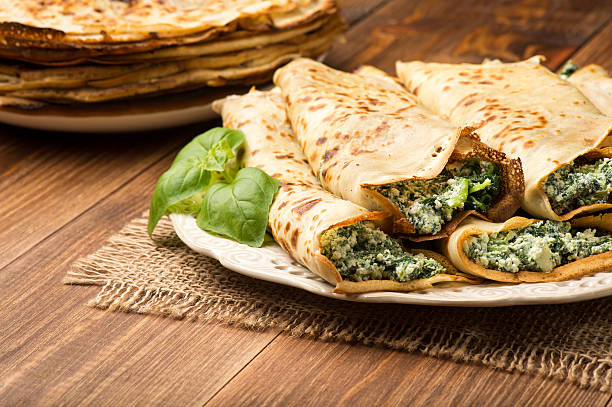 pancakes filled  with spinach and cheese  on the wooden surface. - crepe bildbanksfoton och bilder