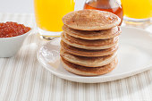 Pancakes meal photographed in studio using natural daylighting.  The pancakes are surrounded by Jam, honey (or syrup) and orange juice. Traditional American breakfast. Sparse composition. Still life photography. No people. High angle view. Horizontal orientation.