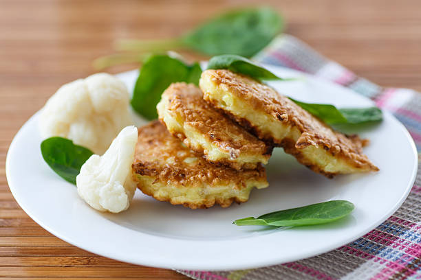 pancakes from cauliflower fried cauliflower fritters on a white plate fritter stock pictures, royalty-free photos & images