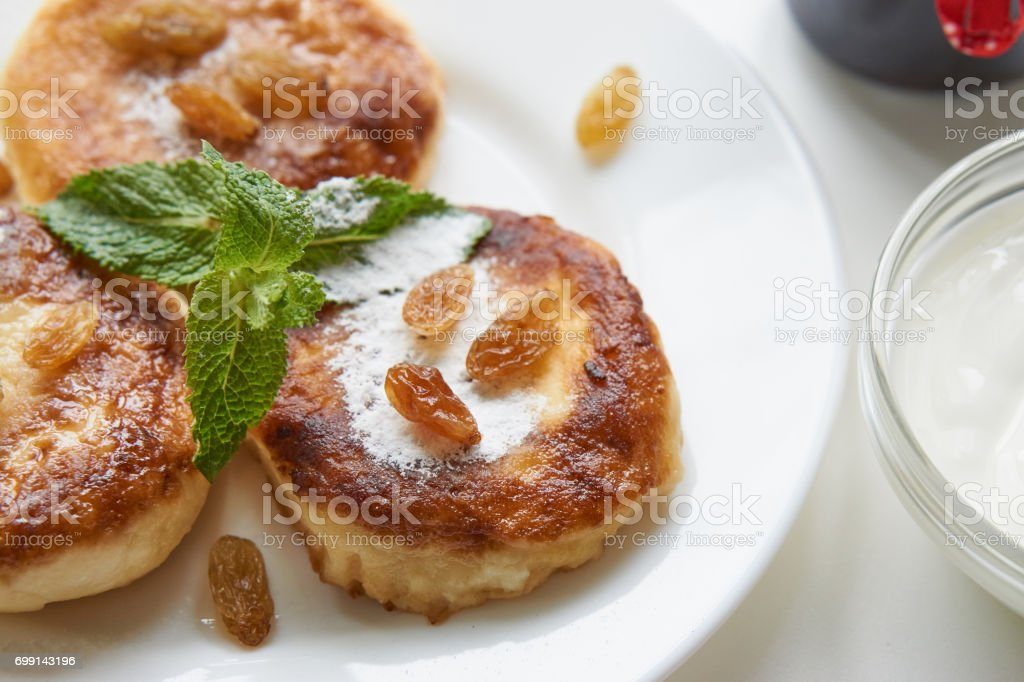 pancakes on a white plate on a white table with jam jar stock photo