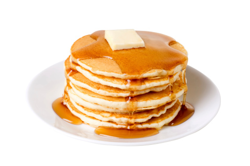 A stack of pancakes on a plate with syrup and butter.  Isolated on white with clipping path.