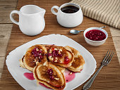 On a white porcelain plate lie rosy pancakes stuffed with currant jam and sprinkled with walnuts