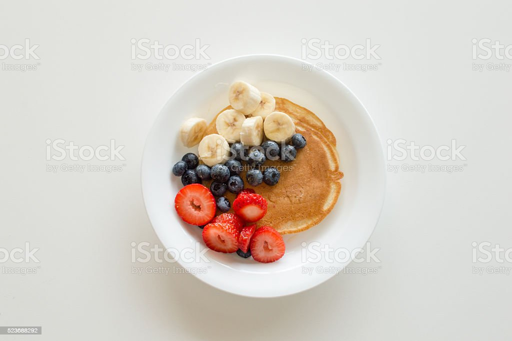 Pancakes with banana, blueberries and strawberries stock photo