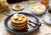 Pancakes with banana, nuts and honey, served with tea. Rustic style, selective focus.