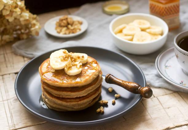 pfannkuchen mit bananen, nüssen und honig, mit tee serviert. rustikalen stil. - gebackene banane stock-fotos und bilder