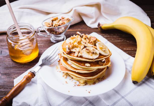 pfannkuchen mit bananen, walnüssen und honig - gebackene banane stock-fotos und bilder