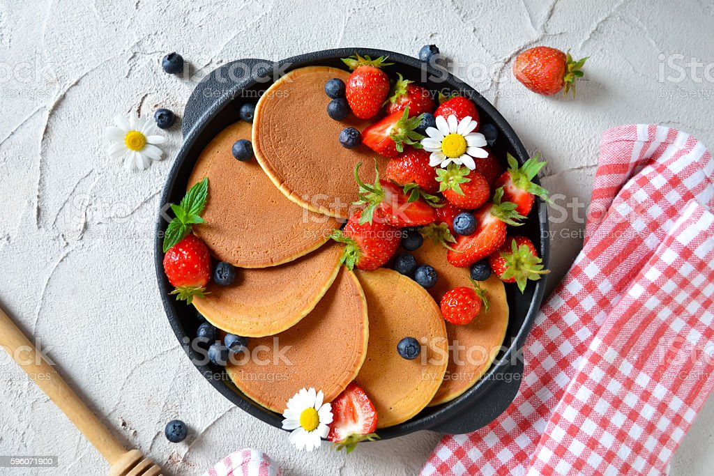 Pancakes with berries and honey in a pan royalty-free stock photo