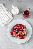 Pancakes with berries and sweet jam on grey concrete background. Top view